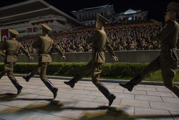 Goose-stepping soldiers mark the beginning of a massive torchlight parade to commemorate the 1948 founding of the Democratic People's Republic of Korea.