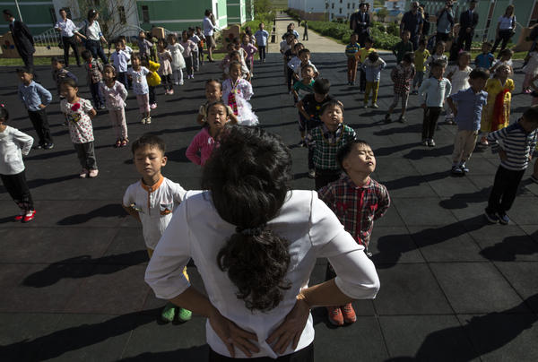A teacher leads students in singing and dancing outside a school on a communal farm in Pyongyang, as foreign journalists observe.