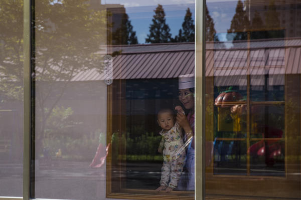 A woman brings a young child to the window to see visiting journalists at a nursery on the grounds of a cosmetics factory in Pyongyang.
