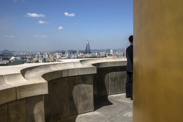 A view of central Pyongyang from the top of Juche Tower, a monument dedicated to the state ideology of self-reliance. The tower is about 3 feet taller than the Washington Monument. A government-provided guide stands at the balcony. In the distance is the 105-story Ryugyong Hotel, which has been under construction for more than 30 years.