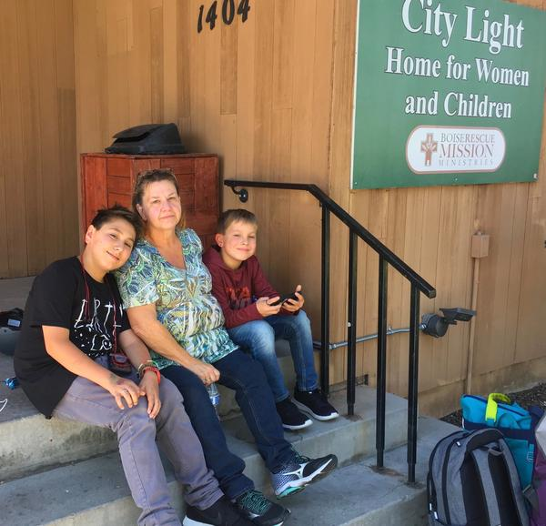 Caydden, 14, and Keston Zimmerman, 11, sit outside a homeless shelter in Boise, Idaho,  with their grandmother Pam Cantrell. They've been searching for housing for three months.