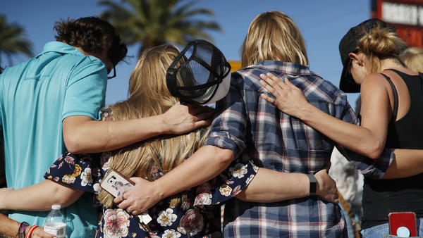 People pray at a makeshift memorial for victims of the Oct. 1 2017, mass shooting in Las Vegas.