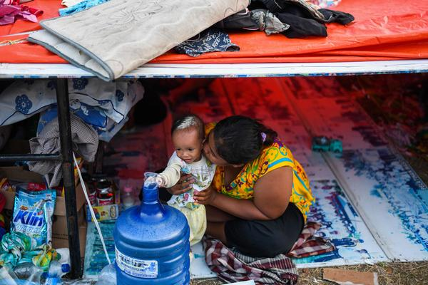 A mother and her child sit in a tent at a makeshift camp in Palu. The Indonesian government said Tuesday that the death toll from the devastating quake and tsunami on the island of Sulawesi had risen to over 1,200 people, up from the previous count of 844.