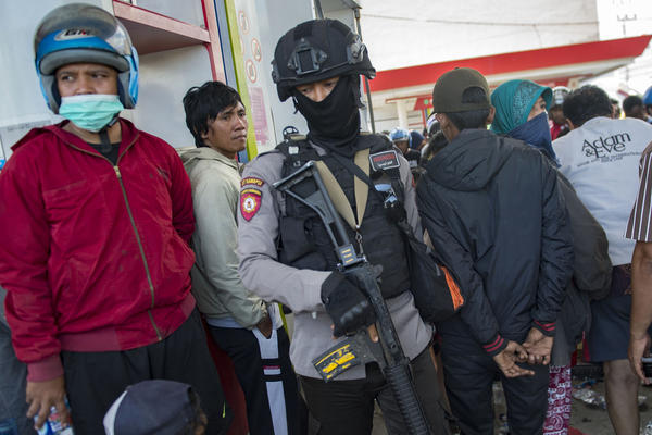 An armed policeman stands guard at a Palu gas station as people wait to obtain gasoline.