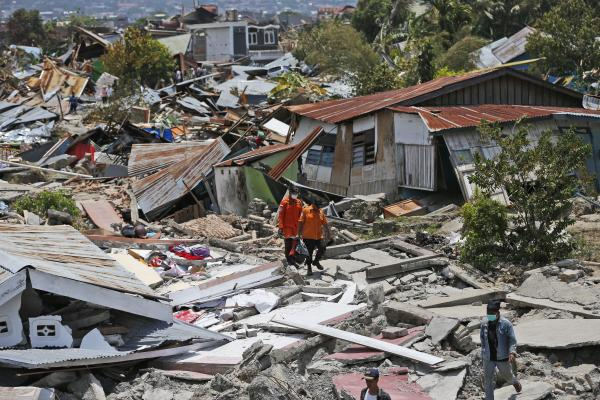 Rescuers carry a body bag containing the remains of an earthquake victim through a neighborhood flattened by last week's earthquake in Palu, Central Sulawesi, Indonesia, Tuesday.