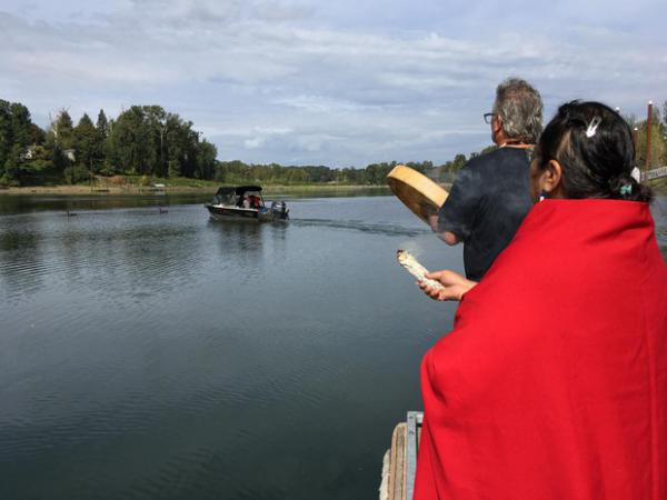 <p>Grand Ronde Tribal Chairwoman Cheryle Kennedy and Tribal Secretary Jon A. George watch as tribal employees launch a boat to build a fishing platform at Willamette Falls.</p>