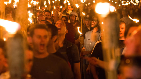 "White supremacists march through Charlottesville, Va., the night before the ""Unite the Right"" rally in August 2017. Federal agents have arrested four men on riot charges connected to the rally."
