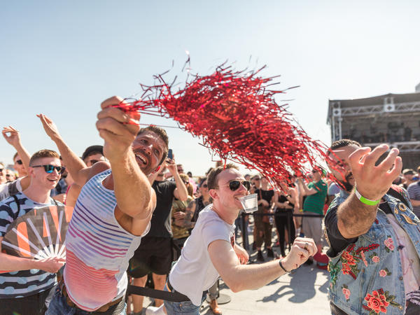 Attendees fight for a wig fired from a T-shirt cannon by actors Neil Patrick Harris and David Burkta.