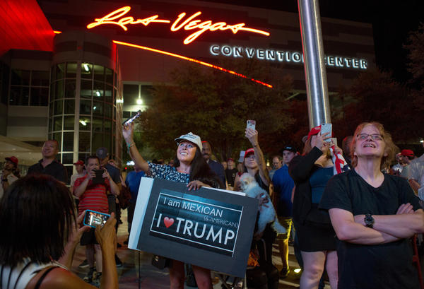 Supporters gather outside the Las Vegas Convention Center as they watch President Trump's rally on screens in the parking lot on Sept. 20.