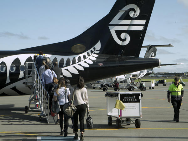 Passengers board an Air New Zealand flight at Christchurch Airport in New Zealand in 2017. A new law says arriving travelers may be fined for failing to provide a passcode or fingerprint to unlock electronic devices for customs agents.