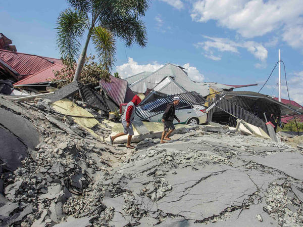 Men walk on a damaged road in the Petobo subdistrict on Tuesday, days after an earthquake and tsunami hit Palu in Central Sulawesi, Indonesia.