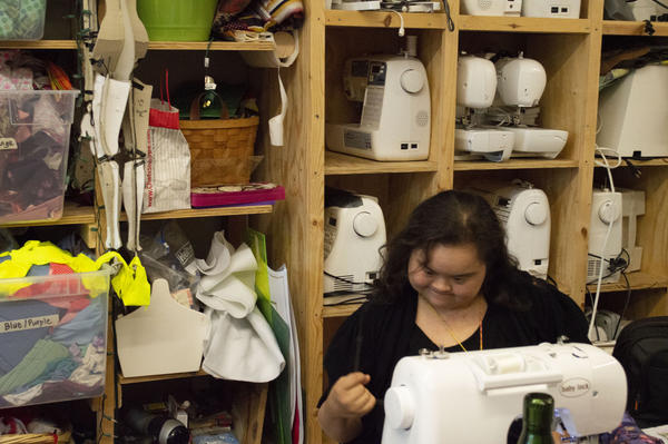 Designer Melelani Perry sews a fashion design she's been working on at Living Arts Studio.