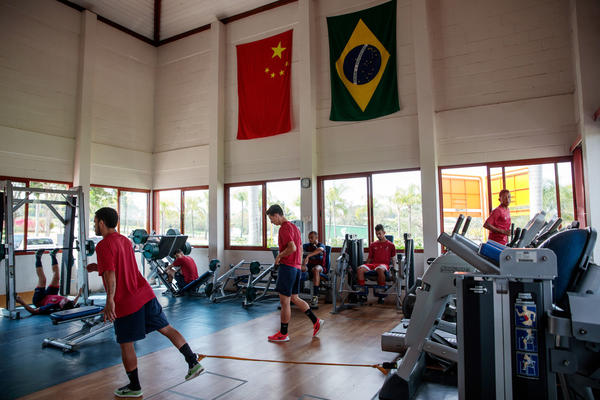 Chinese players work out under Chinese and Brazilian flags on display in Desportivo Brasil's gym.
