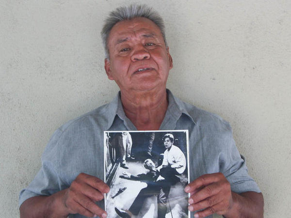 Juan Romero earlier this year at his home in Modesto, Calif., holding a photo of himself and Sen. Robert F. Kennedy, taken by <em>The Los Angeles Times' </em>Boris Yaro on June 5, 1968. Romero died this week at age 68.