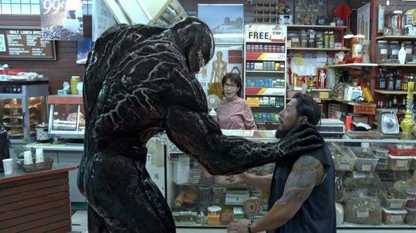 Venom (a CGI-enhanced Tom Hardy) invites a robber (Sam Medina) out for a bite, while the bodega-keeper (Vickie Eng) looks on.