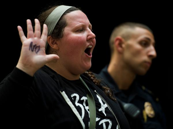 "A demonstrator raises her hand, on which the word ""no"" is scrawled in black. She was one of many demonstrators clad in black who packed the Hart building Thursday in protest of Kavanaugh's nomination."