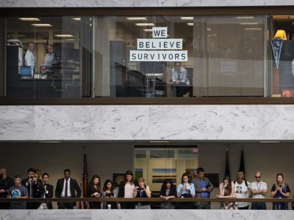 Senate staffers watch from the upper-floor offices as demonstrators below them protest Kavanaugh.