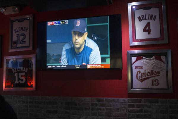 Red Sox manager Alex Cora is seen on a TV in his hometown of Caguas, Puerto Rico, during a game against the Indians. On the wall around the TV are other baseball players' jerseys. (Jesse Costa/WBUR)