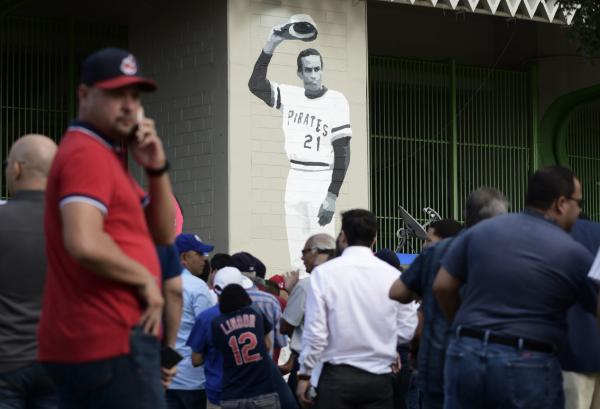 A mural of Puerto Rican professional baseball right fielder Roberto Clemente decorates Hiram Bithorn Stadium where fans wait to enter the final game of a two-game Mayor League Series between the Minnesota Twins and the Cleveland Indians in San Juan, Puerto Rico, Wednesday, April 18, 2018. (AP Photo/Carlos Giusti)