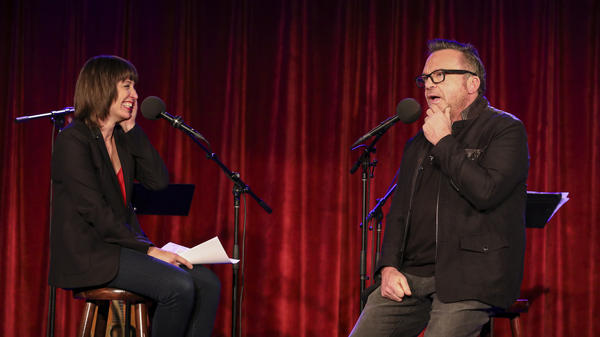 Ophira Eisenberg chats with Tom Arnold on <em>Ask Me Another</em> at the Bell House in Brooklyn, New York.