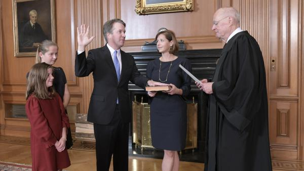 Retired Justice Anthony Kennedy administers the Judicial Oath to Judge Brett Kavanaugh in the Justices' Conference Room of the Supreme Court Building. Ashley Kavanaugh holds the Bible. At left are their daughters, Margaret, background, and Liza.