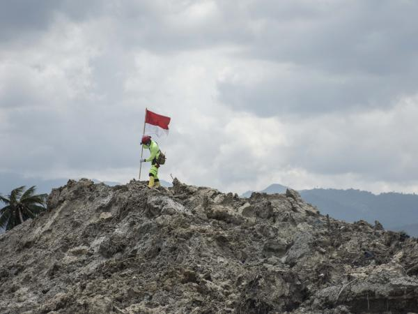 A rescue worker hoists an Indonesian flag atop a mound of mud in the Petobo neighborhood of Palu. Flags usually mark the spot of dead body, later to be retrieved.