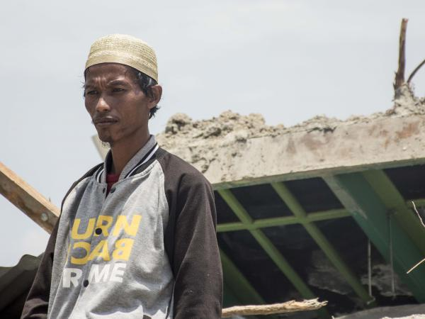 Muhlis Ipul, 32, stands before the remains of his modest home in Petobo, where the earthquake swept away his wife and two daughters. Ipul says his most painful memory is his youngest daughter, Windy, slipping from his grasp as they ran from their house, and he tumbled head over heels as the asphalt buckled beneath him.
