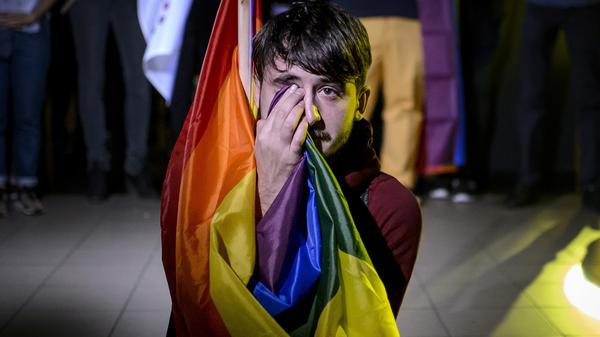 A man sits draped in a rainbow flag in a nightclub in Bucharest, Romania on Sunday after learning election results. A referendum to redefine marriage as between a man and a woman failed to attract the minimum number of voters and the result was invalidated.