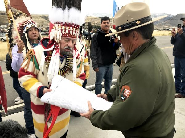 Chief Stanley Charles Grier hands over a declaration to Yellowstone deputy superintendent Pat Kenney
