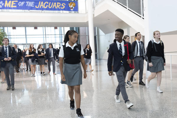 Starr Carter (played by Amandla Stenberg, left) is a black student in a primarily white prep school in <em>The Hate U Give.</em>