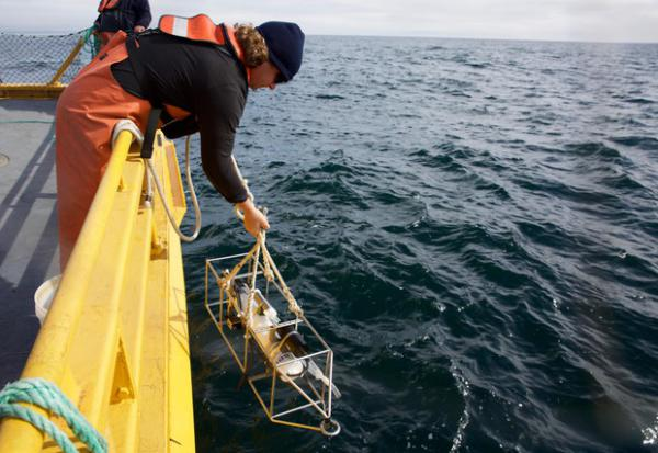 <p>A deck hand lowers scientific equipment into the Pacific to check the health of scanners sitting on the ocean floor</p>