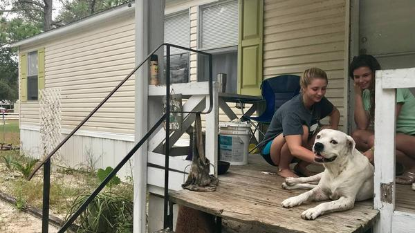 Jenna Clark, left, pets her family's pit bull, Buster, with a friend. Clark, 18, said her family will stay in their mobile home in Panacea during Hurricane Michael.