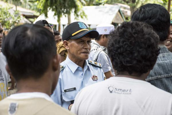 "Safiuddin, head of the Donggala District Prison, addresses the returning inmates assembled in the prison yard.  He exhorts them to ""encourage your fellow inmates to turn themselves in,"" and tells the inmates who have freely come back to ""serve your sentence, and live out your life without worry."""