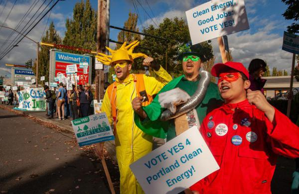 <p>Supporters of Measure 26-201 rally outside of Walmart and U.S. Bank branches in East Portland on Oct. 9, 2018.</p>