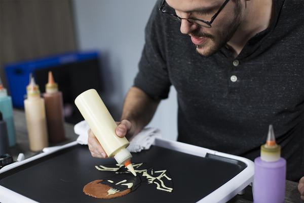 Daniel Drake creates pancake art using a grill from Dancakes' griddle kit.