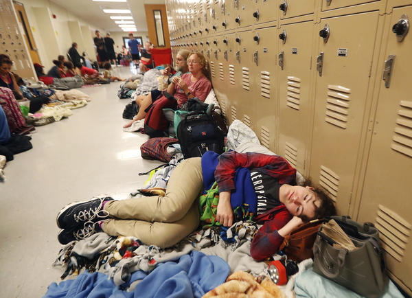Emily Hindle lies on the floor at an evacuation shelter set up at Rutherford High School, in Panama City. The storm devastated some areas and left others relatively unscathed.