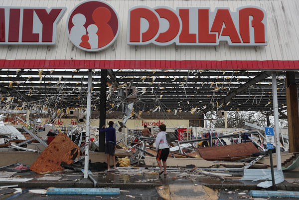 People look on at a damaged store after Hurricane Michael passed through on October 10, 2018 in Panama City, Florida.