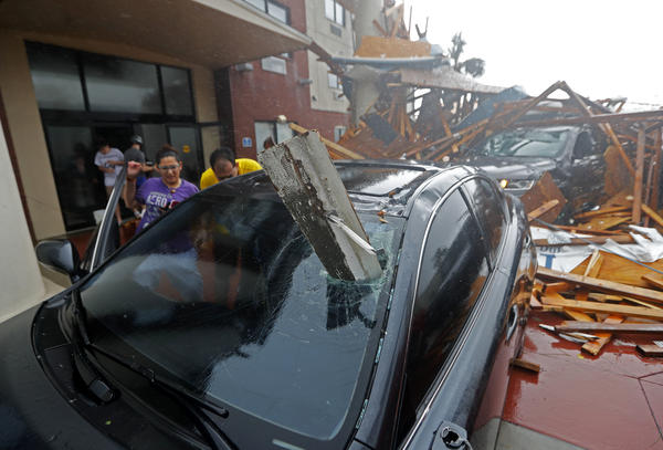 A woman checks on her vehicle as Hurricane Michael passes through, after the hotel canopy had just collapsed, in Panama City Beach, Fla., Wednesday, Oct. 10, 2018.