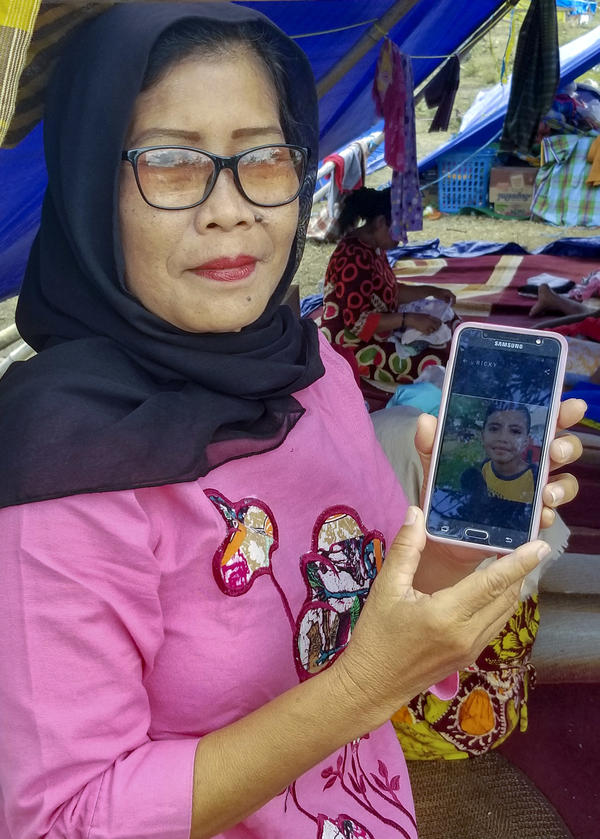 Evi Raharuddin, 54, shows a photo of her 9-year-old grandson, Raldi, who disappeared when the family ran from their house in the earthquake on September 28.