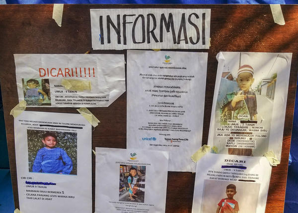 Photos of missing children are displayed on a bulletin board at an encampment in Palu run by Save the Children and UNICEF.