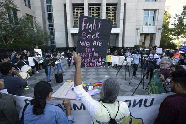 In this June 20, 2018, file photo, more than 100 protesters demonstrate outside the federal courthouse where a federal judge heard arguments over the U.S. Justice Department's request to block three California laws that extend protections to people in the country illegally, in Sacramento, Calif. (Rich Pedroncelli/AP)