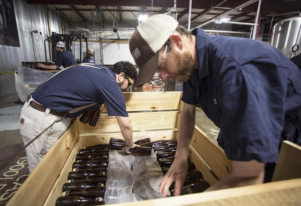 Allagash employees Salim Raal, left, and Brendan McKay stack bottles of Golden Brett, a limited release beer fermented with a house strain of Brettanomyces yeast. The Maine brewery recently installed solar panels as part of its sustainability initiatives.