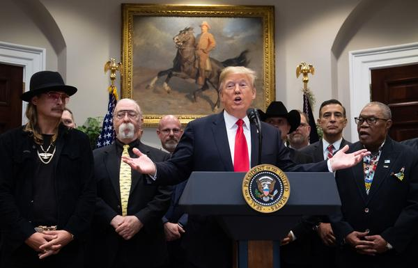 President Trump speaks alongside musician Kid Rock (left) and musician Sam Moore (right) prior to a bill signing at the White House on Thursday.