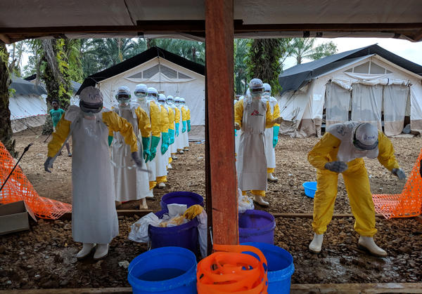 Health workers remove their protective suits at a treatment center set up by Doctors without Borders in Mangina, a town in the Democratic Republic of the Congo.