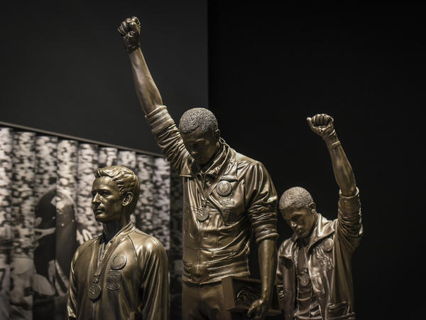 A statue depicting U.S. track and field athletes Tommie Smith (center) and John Carlos (right) as they raised gloved fists during their medal ceremony at the 1968 Summer Olympics is housed in the Sports Galleries at the Smithsonian Institute's National Museum of African American History and Culture.