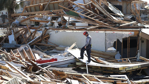 A member of a Florida task force searches the ruins in Mexico Beach, Fla., after Hurricane Michael.