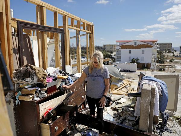 Candace Phillips sifts through what was her third-floor bedroom while returning to her damaged home in Mexico Beach, Fla.