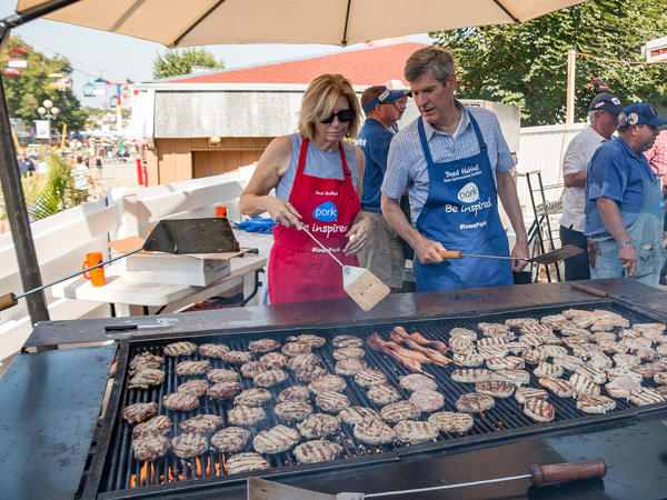 Iowa Democratic gubernatorial candidate Fred Hubbell and his running mate, state Sen. Rita Hart, flip meat at the Iowa Pork Producers tent at the Iowa State Fair.