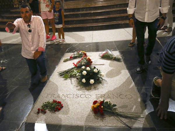 A man does a fascist salute as he stands next to the tomb of Francisco Franco inside the basilica at the Valley of the Fallen monument outside Madrid. Spain's center-left government approved legal amendments that it says will ensure that Franco's remains can soon be dug up and removed.