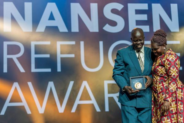 Evan Atar Adaha, surgeon and medical director at a hospital in South Sudan, accepts the U.N.'s Nansen Refugee Award in Geneva, on October 1. His wife, Angela Atar, is at right.